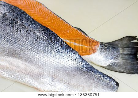 Meat of fish without bones. Raw fish on beige background. Salmon caught at the sea. Ingredient for salad or soup.