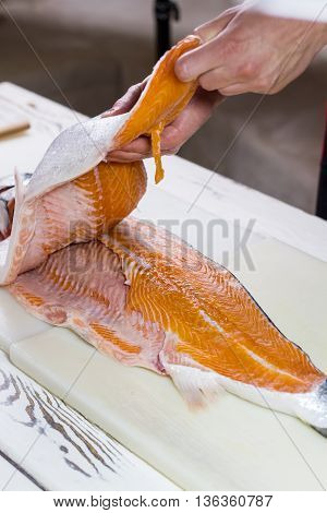 Male hands touch fish meat. Sliced fish on cooking board. Chef takes fish for sushi. Meat of sea salmon.