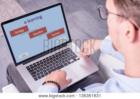 young man is looking on e-learning app at home
