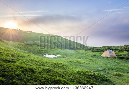 Sunrise in mountains with a tourist tent and a little lake in view