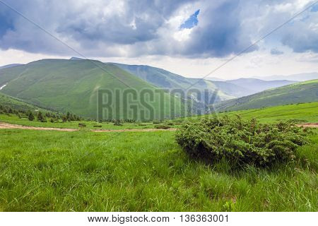 Sharp green mountain peaks and sky with dramatic clouds landscap