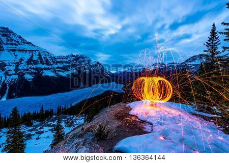 circle of burning steel wool in the winter above frozen peyto lake.