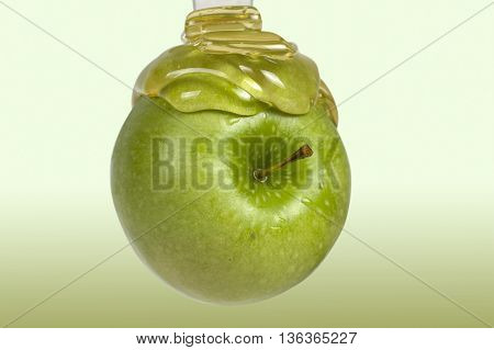 honey flowing on a green apple. Honey and apple.