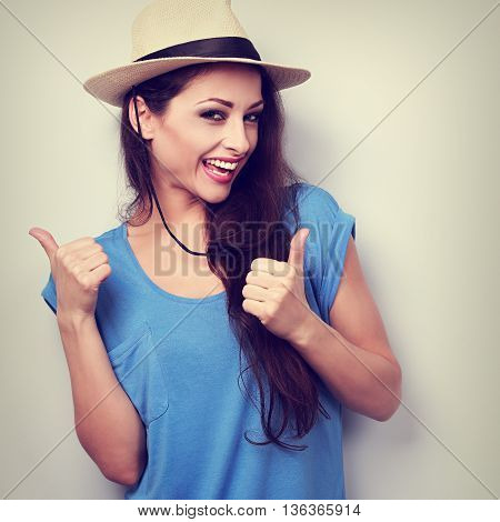 Optimistic Casual Woman In Blue Top And Hat Showing Thumb Up By Two Hands With Happy Emotion. Vintag