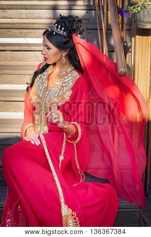 Beautiful Young Woman In Oriental Dress Sitting On The Stairs