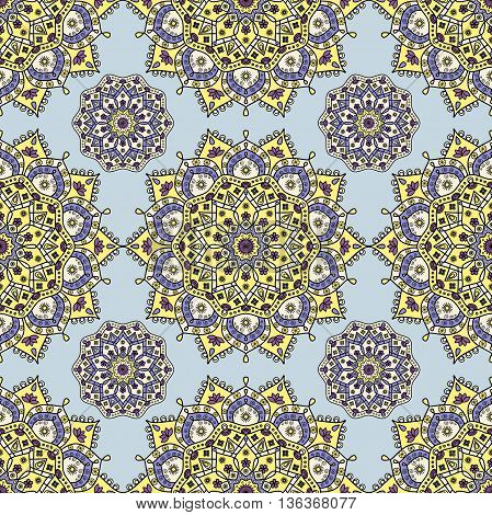 Seamless floral mandala pattern in yellow, blue & creamy white on pale aqua blue background. Decorative vintage pattern for paper & textile prints of sari & sarong style garment layouts.