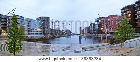 Hamburg Germany - May 25 2008: Hamburg Hafencity panorama on a rainy day. Channel in foreground surrounded by modern brick buildings
