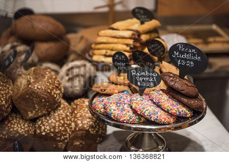 Sprinkles and Chocolate cookie display with bread in a shop
