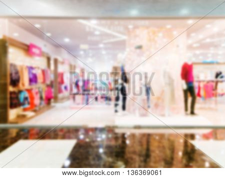 Blur image of window bright display with four mannequins wearing red dress with text Sale