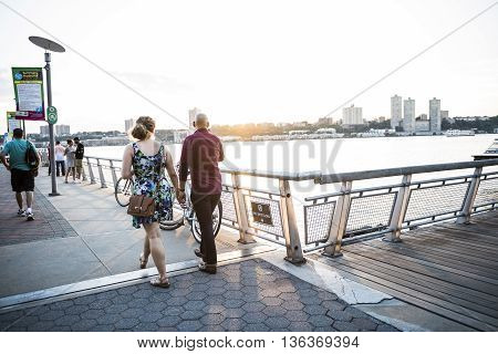 New York, USA - June 18, 2016: A couple walking down the boardwalk of riverside park pier 1 in New York City with view of New Jersey