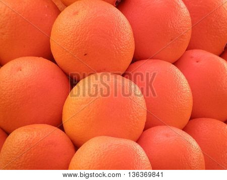 Ripe oranges at a farm stand in a big pile.