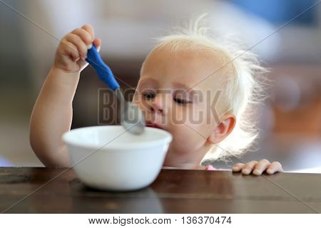 One Year Old Baby Girl Eating Cereal With A Spoon At Home