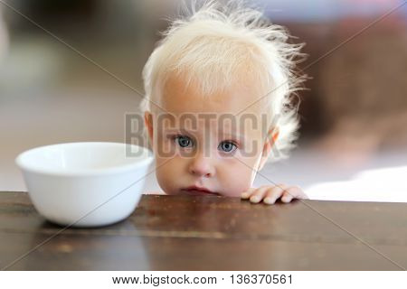 A sad little one year old baby girl is peeking over the kitchen table looking hungry next to a white empty cereal bowl.