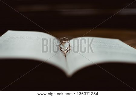 Two golden wedding rings lying on a Bible