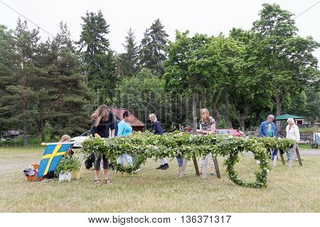 VADDO SWEDEN - JUNE 23 2016: Woman and children making the maypole making the maypole before raising it celebrating the Midsommer in Sweden June 23 2016