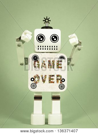 robot toy holding a sign  GAME OVER