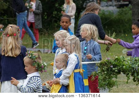 VADDO SWEDEN - JUNE 23 2016: Children wearing traditional costume and flowers in the hair making the maypole celebrating the Midsommer in Sweden June 23 2016