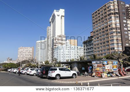 DURBAN SOUTH AFRICA - JUNE 26 2016: Motor vehicles parked next to street vendor against city skyline on Golden Mile beach front in Durban South Africa