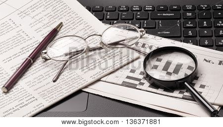 glasses and old newspaper lying on the black open laptop