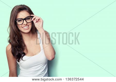 Smiling student girl in white shirt and glasses on green background