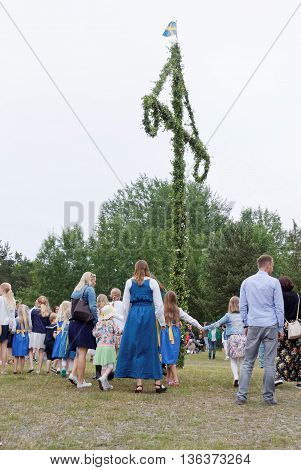 VADDO SWEDEN - JUNE 23 2016: Children and adults dancing around the Maypole celebrating the Midsummer in Sweden June 23 2016