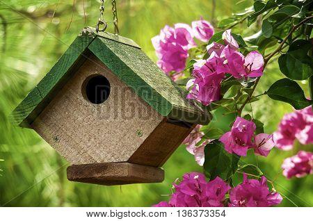 A cute little bird house hanging in a garden.