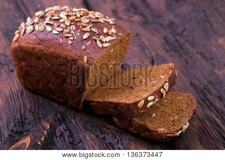 Rye bread with sunflower seeds on an old wooden table