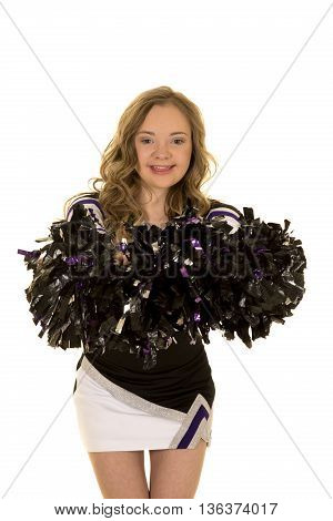 A cheerleader with down syndrome with a big smile on her face holding on to her pom poms.