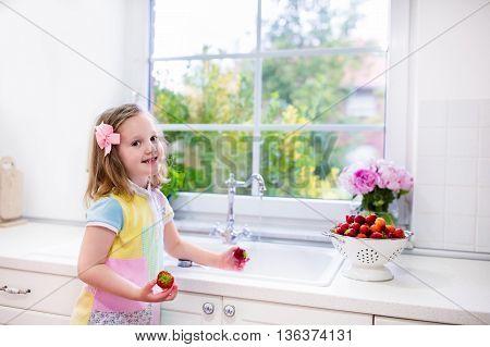 Little Girl Washing Strawberries In White Kitchen