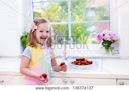 Cute little girl washing fruit in kitchen sink. Child eating strawberry. Kids wash strawberries. Fresh berry for family snack. Healthy nutrition for children. Preschooler kid making breakfast.