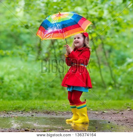 Little girl playing in rainy summer park. Child with colorful rainbow umbrella waterproof coat and boots jumping in puddle in the rain. Kid walking in autumn shower. Outdoor fun by any weather