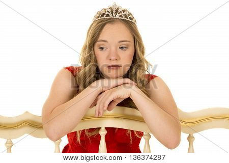 A teen with a sad face in her red dress and crown she has down syndrome