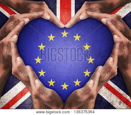 Human hands make heart shape with patterned flag of the European Community inside and the flag of the United Kingdom outside