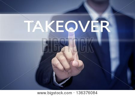 Businessman hand touching TAKEOVER button on virtual screen