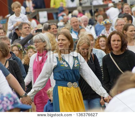 VADDO SWEDEN - JUNE 23 2016: Dancing woman wearing traditional swedish costume dancing around the the maypole celebrating the Midsummer in Sweden June 23 2016