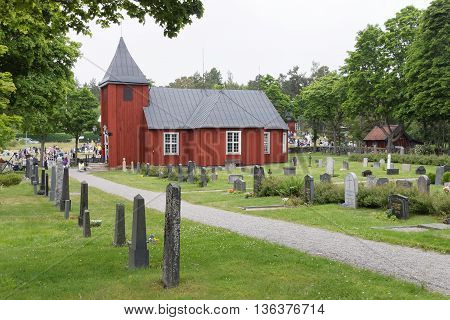 VADDO SWEDEN - JUNE 23 2016: Traditional old wooden red church and a graveyard in Sweden Vaddo June 23 2016