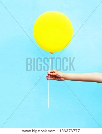 Hand Holding Yellow Air Balloon Over Colorful Blue Background