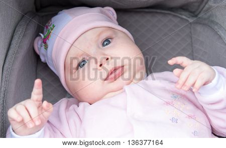 Funny portrait of a newborn baby on a dark background