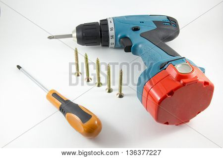 Cordless screwdriver screwdriver and screws on a white background