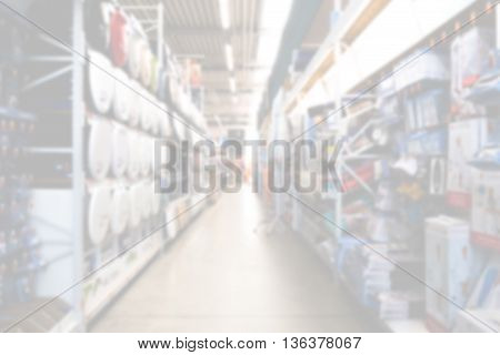 Diy store aisle with shelves of products overexposed and out of focus.