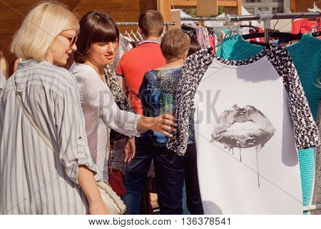 KYIV, UKRAINE - JUN 4, 2016: Two beautiful women watching originaldesigned dress at street fair with fashion stores on June 4, 2016. Kiev is the 8th most populous city in Europe.