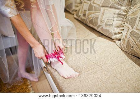 Bride Put On Pink Garter At Her Leg