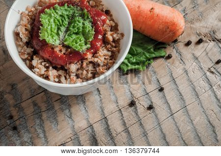 Buckwheat porridge with tomato sauce and leaf salad in a white bowl on a wooden table next to a ceramic bowl with dish is carrots or sliced carrot. Food background. Nice and tasty atmosphere.