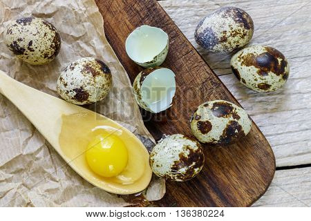 Yolk of quail eggs in a wooden spoon and quail eggs on the table
