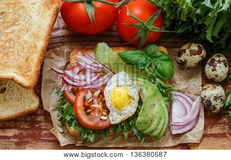 Healthy Breakfast - toast with egg tomato red onion avocado and greens