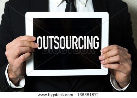 Business man holding a tablet with the text: Outsourcing