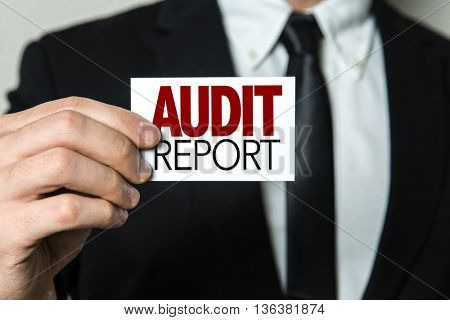 Business man holding a card with the text: Audit Report