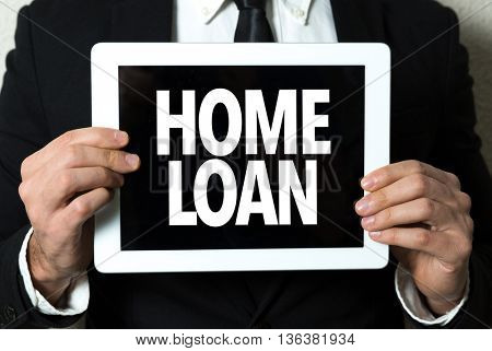 Business man holding a tablet with the text: Home Loan