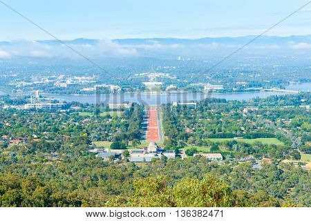 Canberra view from Mount Ainslie aover orange coloured Anzac Parade below to Houses of Parliament and Molonglo River
