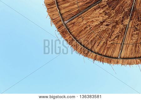 Thatched beach umbrella on clear blue sky background.